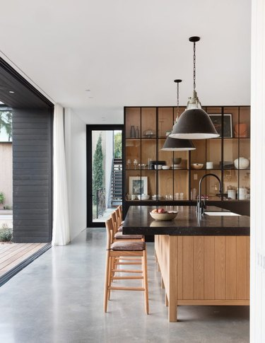 wood and black kitchen with glass front cabinets and concrete floors