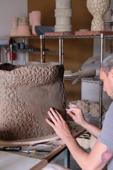 person creating ceramic piece in a studio