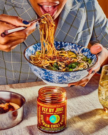 person eating noodles from blue and white bowl with Fly By Jing bottle of chili crisp nearby