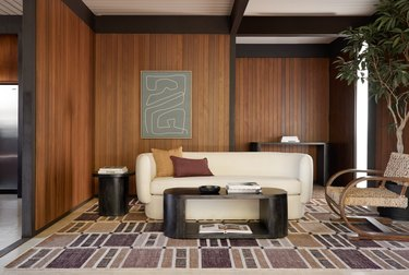 wood-paneled living room with rug