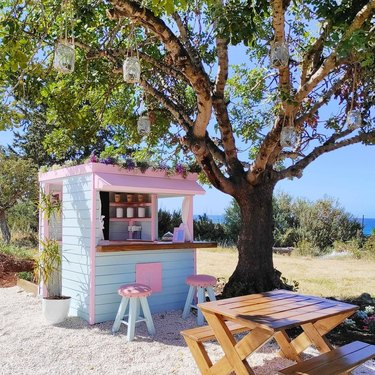 photo of outdoor space with table and playhouse coffee shop in pastel colors