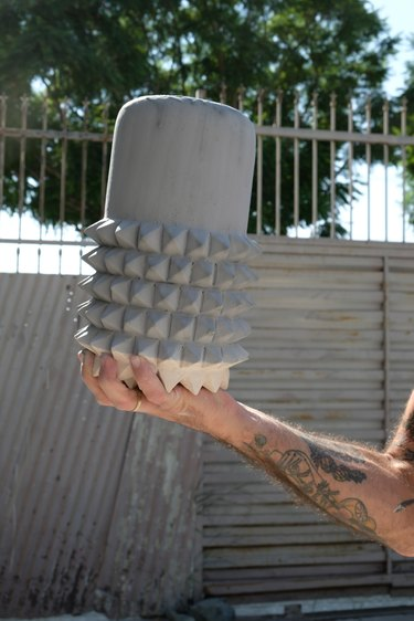 person holding ceramic piece in an outdoor setting with fence and tree in the background