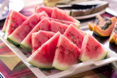 slices of watermelon on plate near other fruit