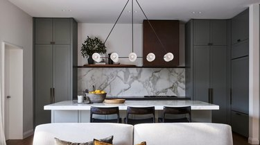 linear-oriented light fixture in sage green kitchen