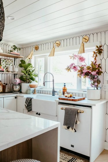 modern brass wall sconces in kitchen with white tile backsplash