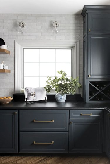 clear glass shade wall sconces in gray and dark blue kitchen