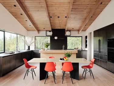 blackened steel kitchen with wood ceiling and orange chairs