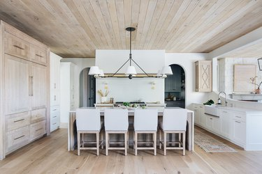 tonal wood forward kitchen with large chandelier over island