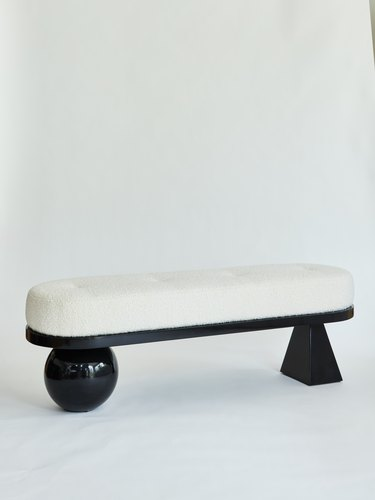 ivory bouclé bench with black legs in round and triangle shapes