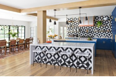 graphic tile kitchen with blue cabinets and slim profile chandelier