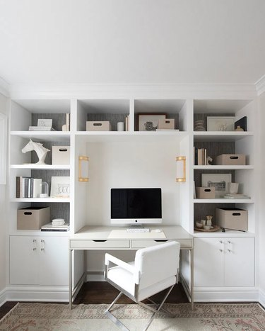 modern white home office with built-in shelving and brass sconces
