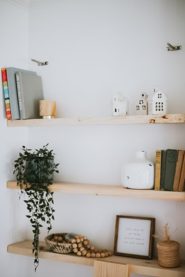 wood floating shelves with decorative items against white wall