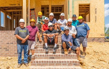 group of construction workers on steps near a house under construction