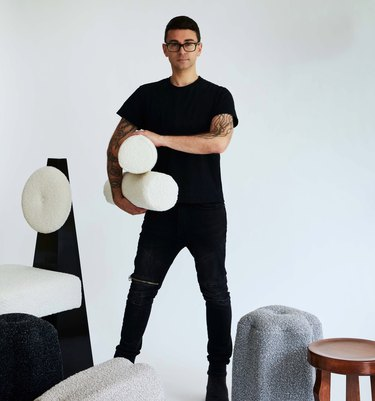Christian Siriano standing with cloth and furniture pieces around him