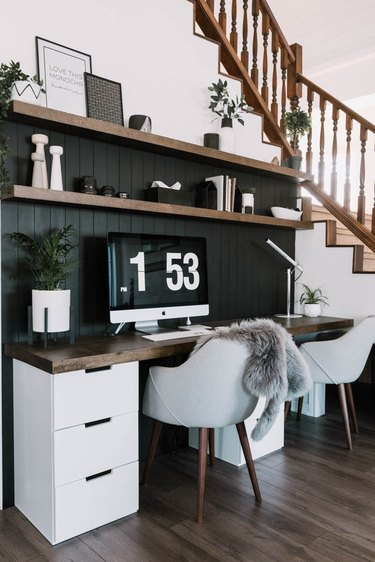 modern home office with black shiplap wall and wood top desk