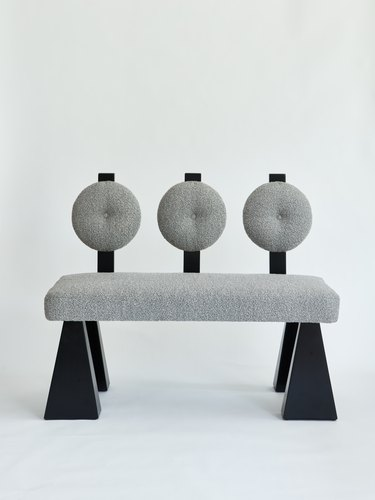 gray bench with round back and black legs