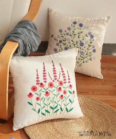 two embroidery pillows on a wood chair