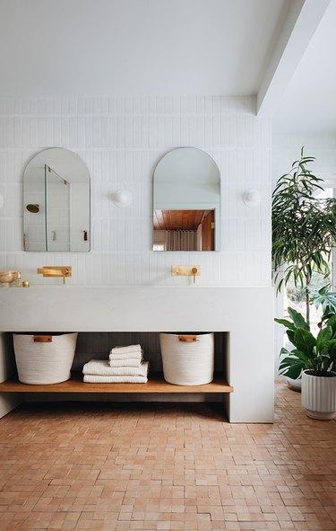 white bathroom with terracotta tile floor