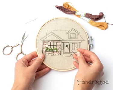 person embroidering a hoop with a pattern of a house, with scissors and thread nearby