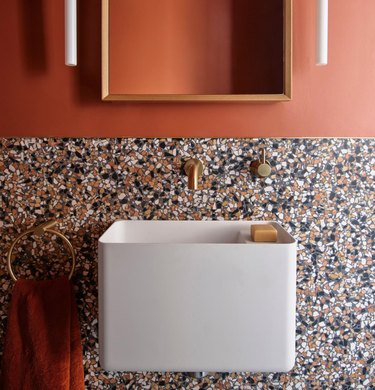 terrazzo backlash with salmon walls and gold hardware