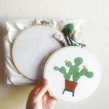 person holding embroidery hoop with cactus pattern near kit with another hoop and embroidery and linen