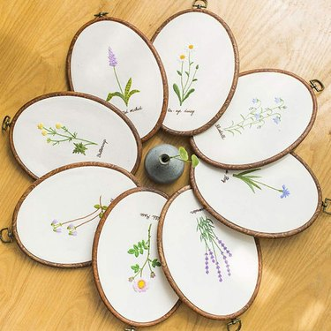a group of oval embroidery hoop with flower patterns arrange in a circle