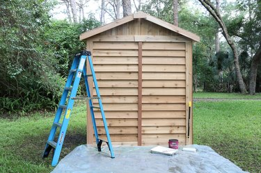 Cedar shed with tarp and ladder and paint supplies