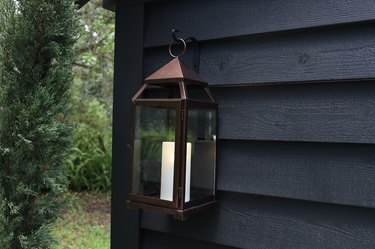 Bronze lantern hanging on black shed with candle inside