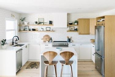 white kitchen with wood midcentury bar stools