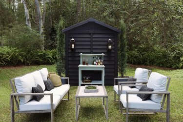 Black painted shed with lanterns serving as cocktail lounge area outside