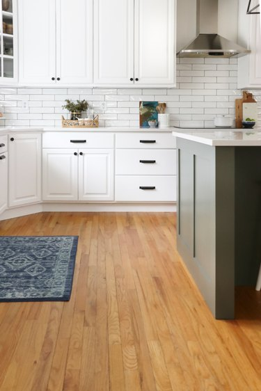 white farmhouse kitchen with white cabinets and green island