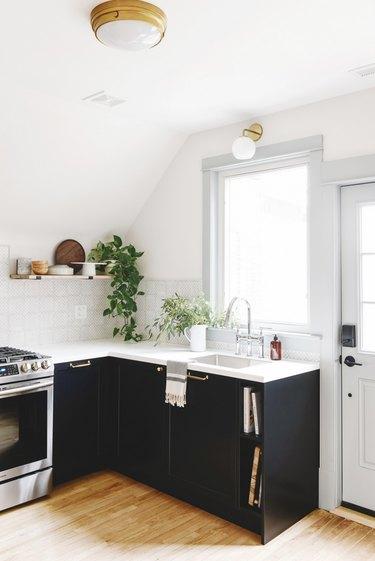 white modern kitchen with black cabinets and patterned backsplash
