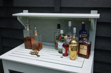 Various alcohol bottles set up on potting bench for cocktail station