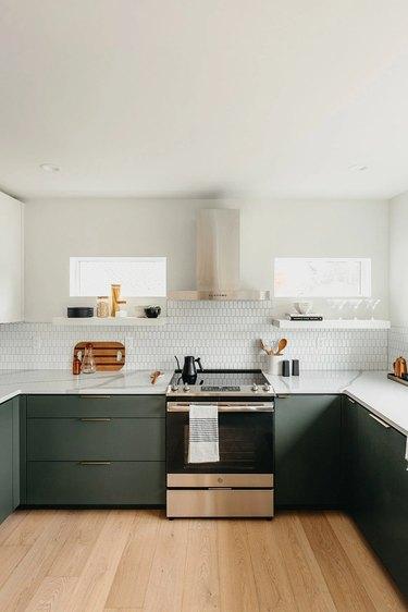 green and white modern kitchen with white tile backsplash