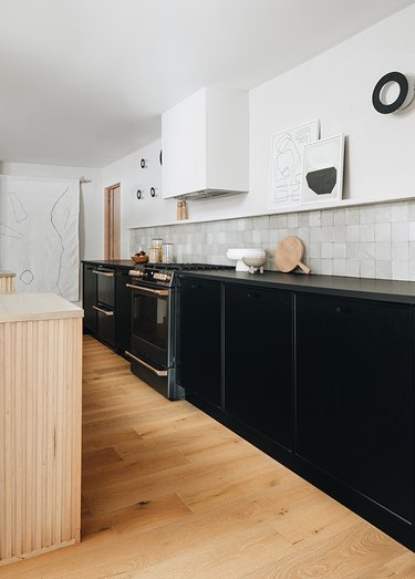 black and white kitchen with black cabinets and white tile backsplash
