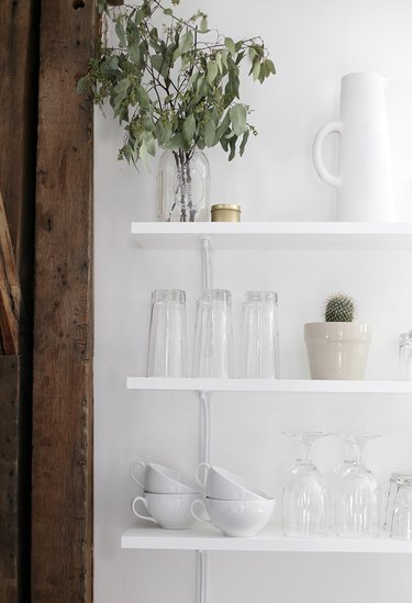 white kitchen with white and clear glassware on open shelves