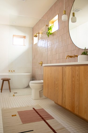 white and pink bathroom with zellige tiles and wooden vanity