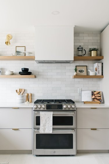 white kitchen with subway tile backsplash and stainless steel stove