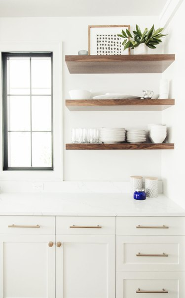 white kitchen with brass cabinet pulls and wood open shelving
