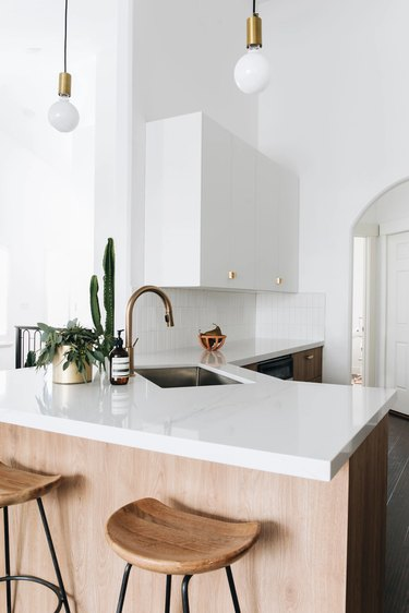 modern white kitchen with glossy white countertop and pendant lights
