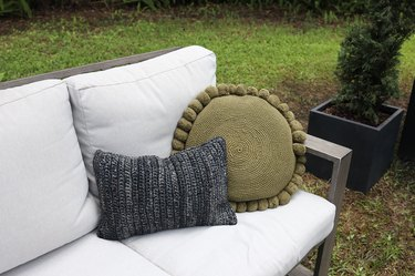 Dark gray lumber pillow and round green pompom pillow on outdoor couch
