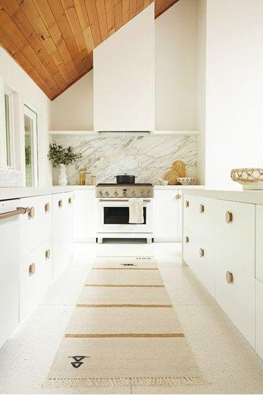 white modern kitchen with striped runner rug