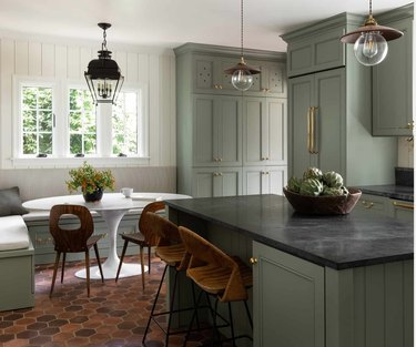 light green kitchen with terracotta flors and banquette