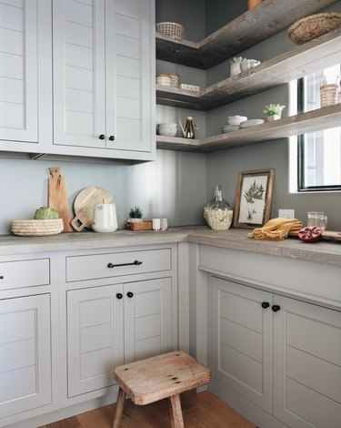 light blue kitchen with cement shelving and countertops