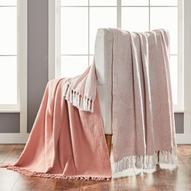 light pink throw blankets hanging over a chair