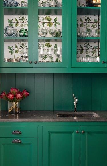 Green kitchen cabinets with matching shiplap backsplash