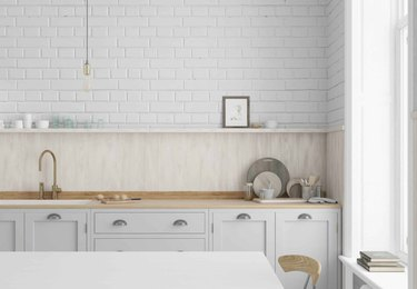 Light gray kitchen cabinets with wood backsplash and brick wall