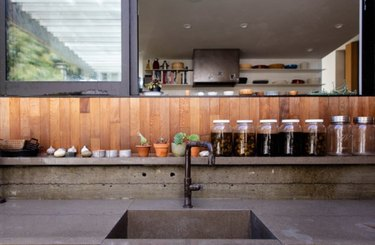 Kitchen with concrete counters and wood backsplash