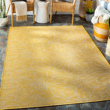 bright yellow area rug with white flower designs