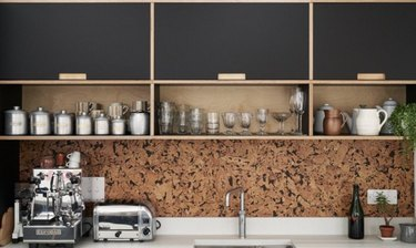 Modern kitchen with black cabinets a cork backsplash